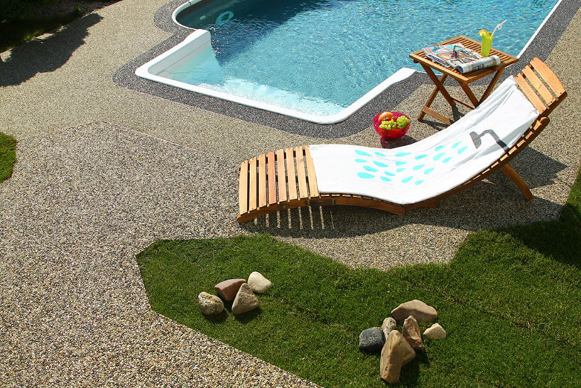 wykładzina zmałych kamyków ułożona obok małego basenu