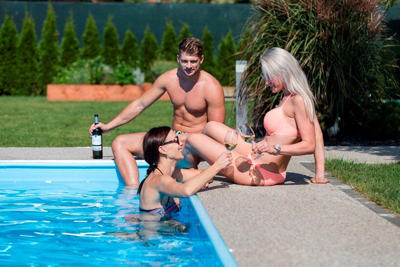 troje osób przy basenie otoczonym kamiennym dywanem