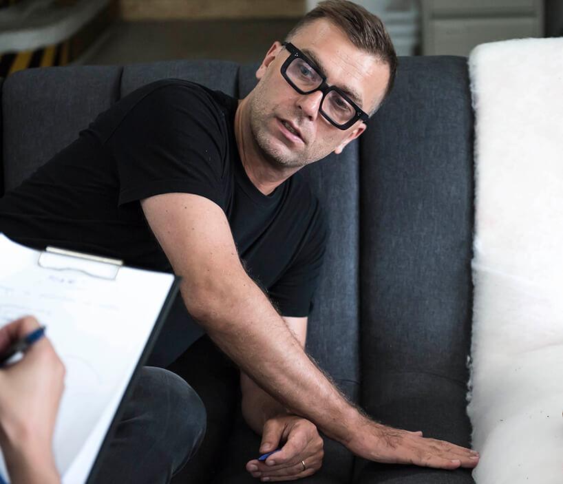 mężczyzna wokularach siedzący na sofie podczas produkcji