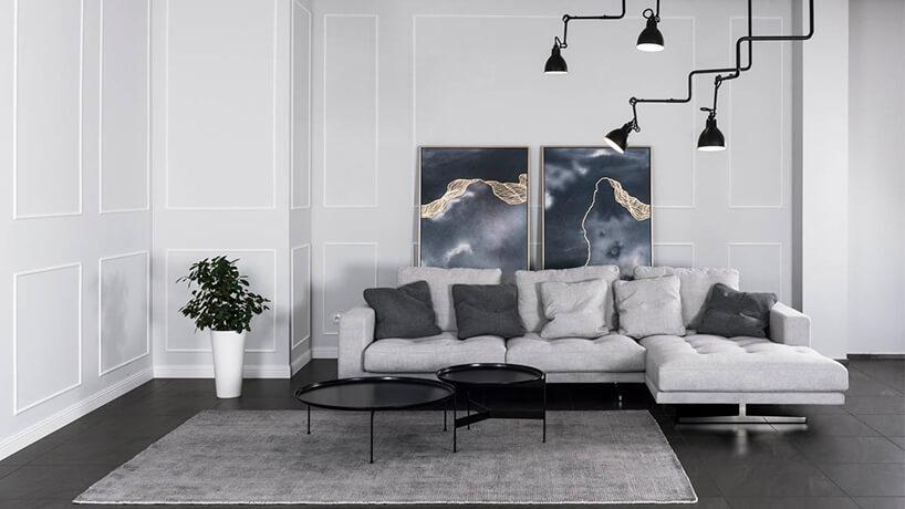 szara sofa narożna wsalonie zczarną podłogą iszarymi ścianami