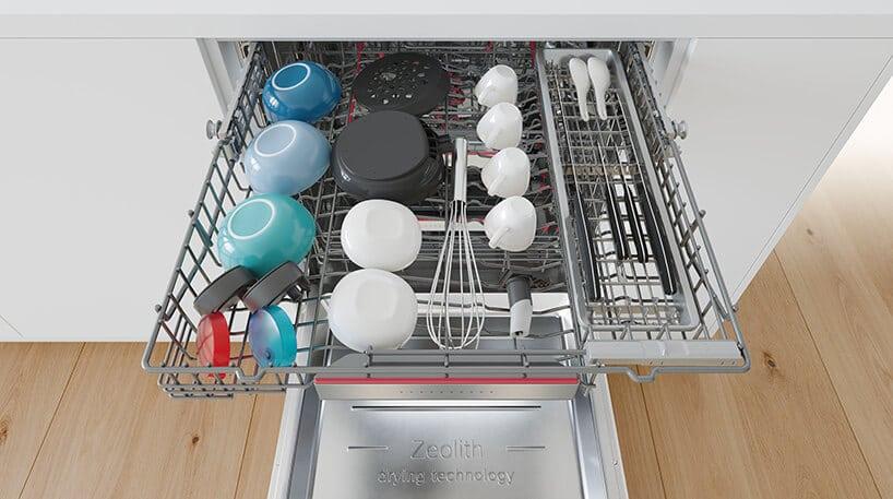 szare wnętrze zmywarki zbiałymi oraz jasno niebieskimi naczyniami wjasnej kuchni