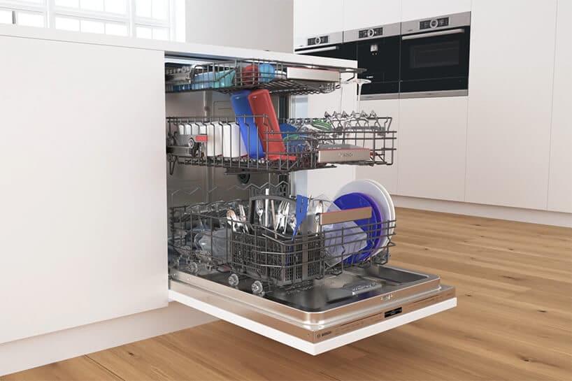 zapakowana zmywarka naczyniami wróżnych kolorach zbiałym frontem obok szafek kuchennych
