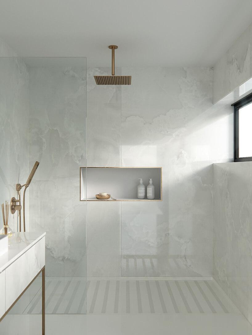 łazienka wykończona białym kamieniem od Cosentino ze złotą deszczownią ipółką wykończoną złotą listwą