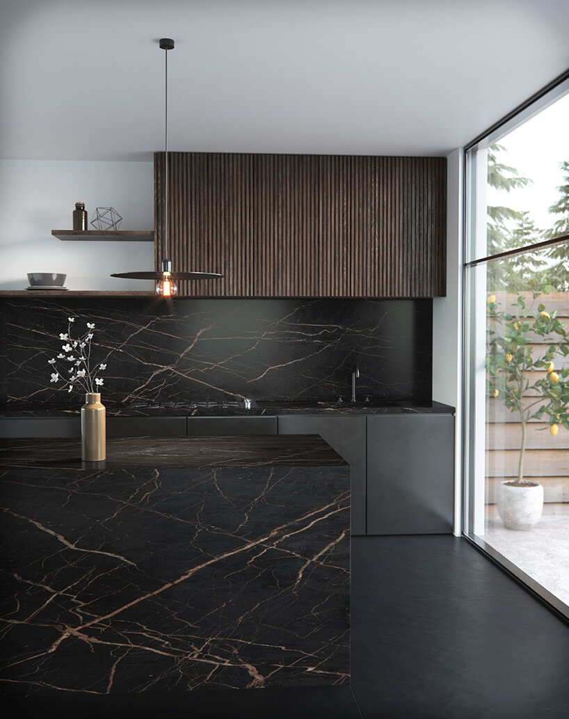elegancka kuchnia zczarną podłogą pod szafkami zczarnymi frontami idużą wyspą wykończoną czarnym kamieniem zbrązowymi pęknięciami