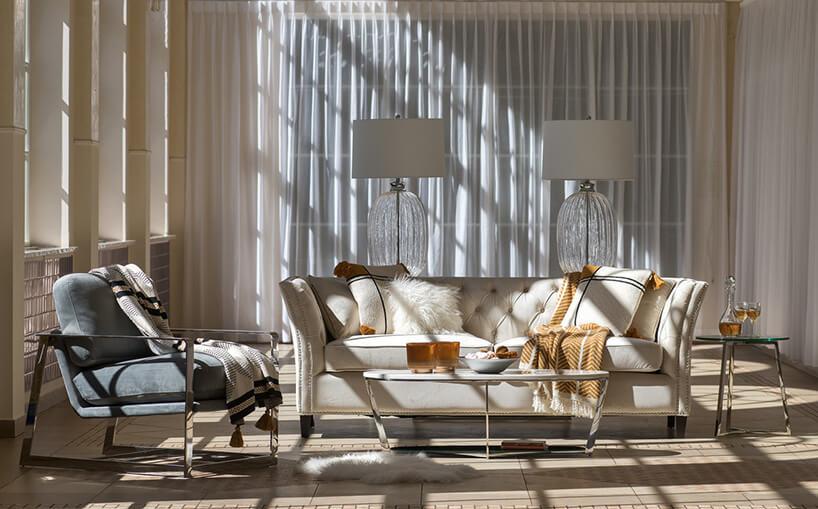 meble na metalowych chromowanych konstrukcjach przy jasnej kanapie zpoduszkami