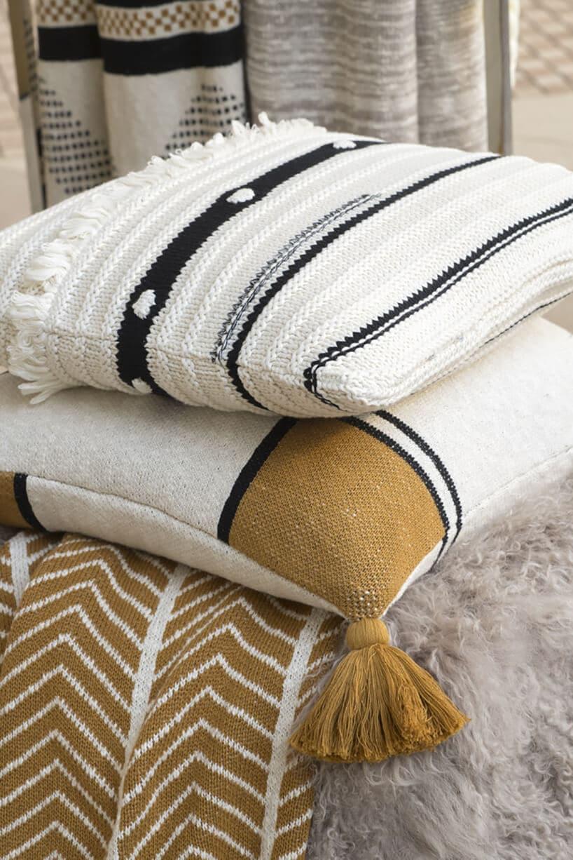 puszyste jasne materiałowe poduszki zciemnymi paskami oraz łatą wkolorze beżu