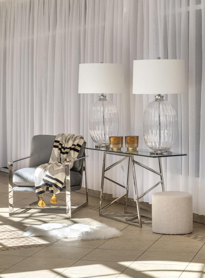 chromowane nogi stolika ze szkłem oraz lampami ze szklanymi wazonami oraz białymi kloszami