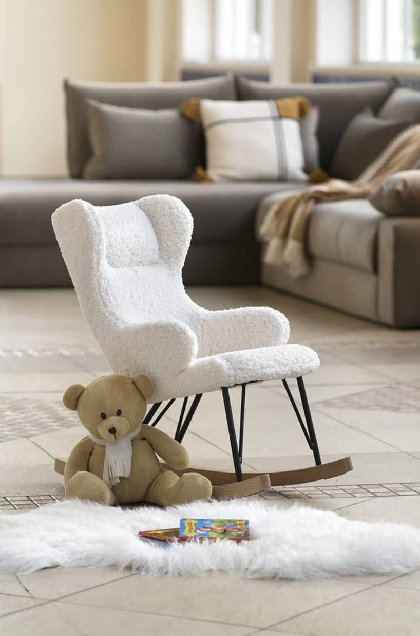 bujany fotel wwersji mi wkolorze bieli oraz mały miś oparty iopłoze