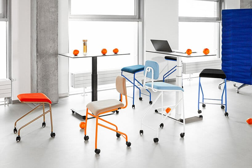 nowoczesne biurowe krzesła zkolorowymi nogami przy cienkich biurkach zkulkami