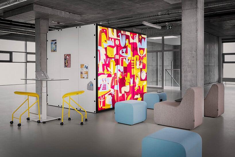 duży kwadrat zkolorową ścianą zczerwonymi elementami przy żółtym krześle iniebieskich kosteczkach