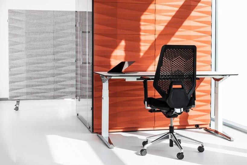regulowane biurko wkolorze stali zczarnym siatkowym fotelem przy pomarańczowym parawanie