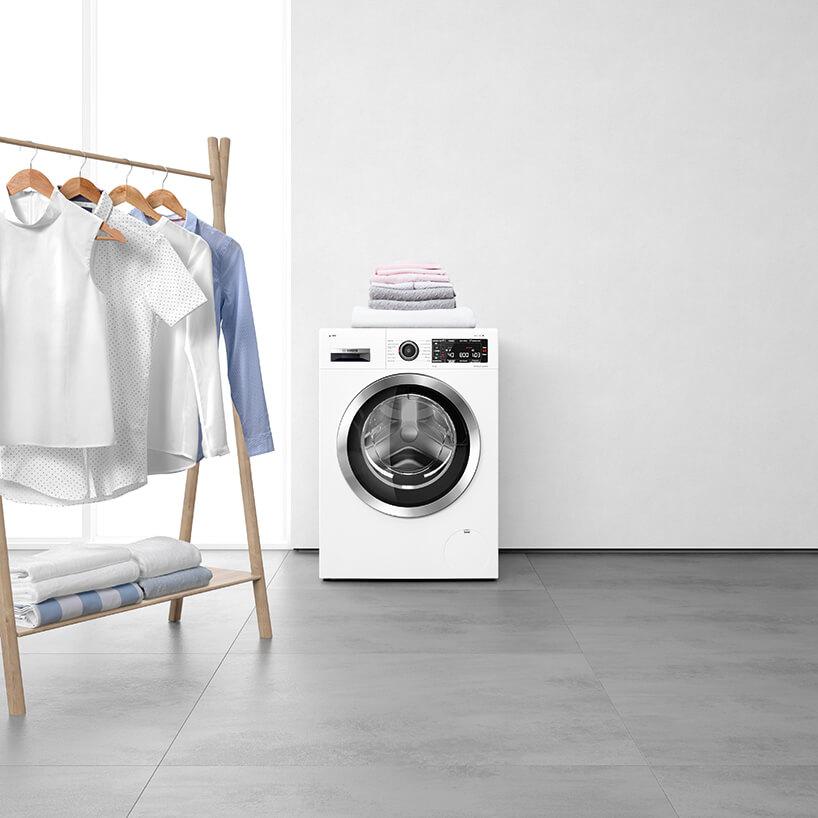 nowczesna suszarka samoczyszcząca Bosch obok drewnianego wieszaka na ubrania