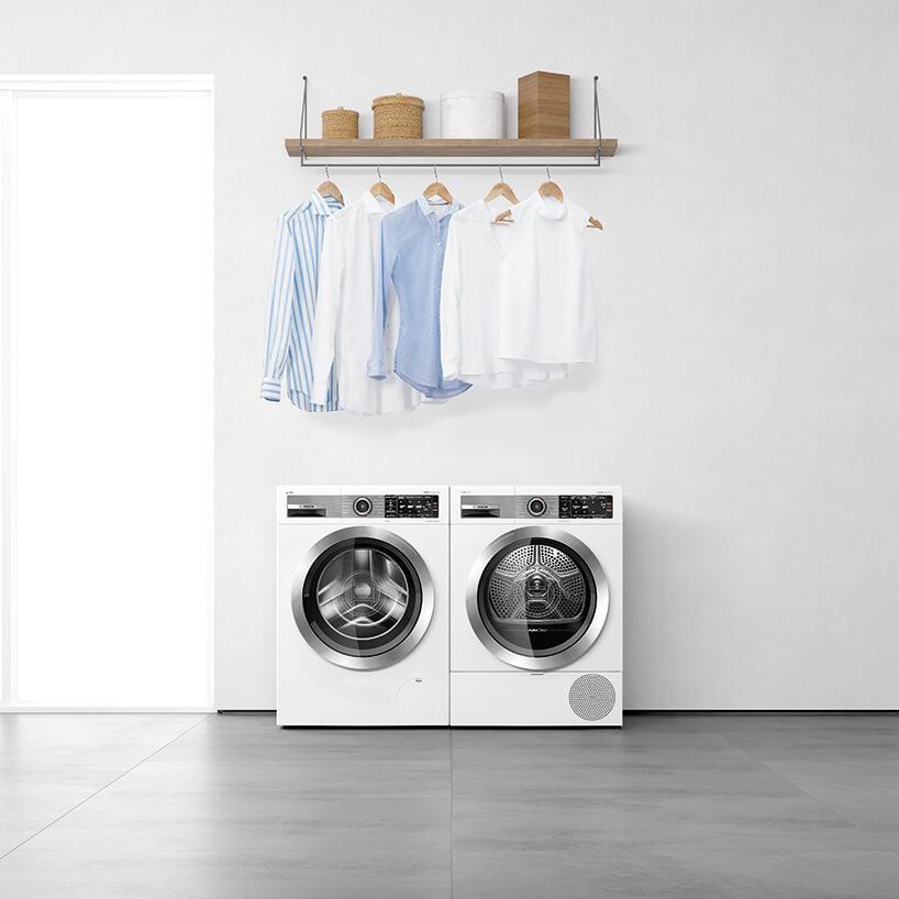 nowczesna suszarka samoczyszcząca Bosch obok nowoczesnej pralki Bosch pod wieszakiem na ubrania zkoszulami