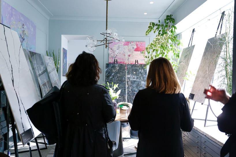 dwie kobiety stojące tyłem na tle gresów zkolekcji Grand Concept od Opoczno
