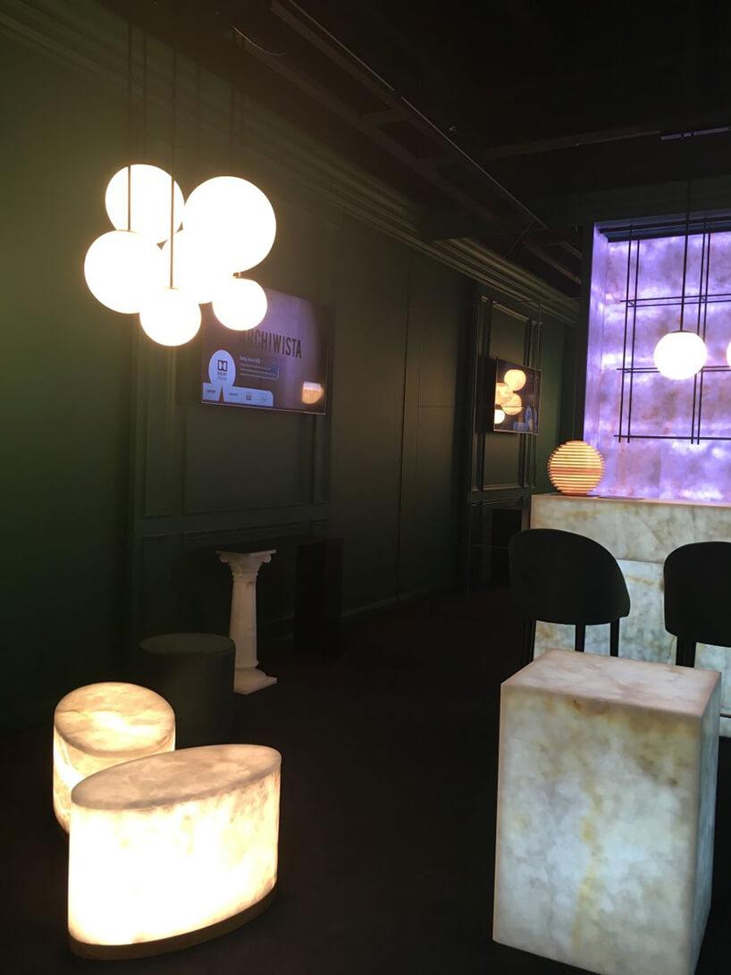 nowoczesna lampa wisząca zklikom kloszami różnej wielkości nad podświetlanymi od środka owalnymi stolikami