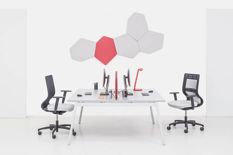 pięć paneli akustycznych od MDD onieregularnych kształtach na białej ścianie nad białym podwójnym biurkiem