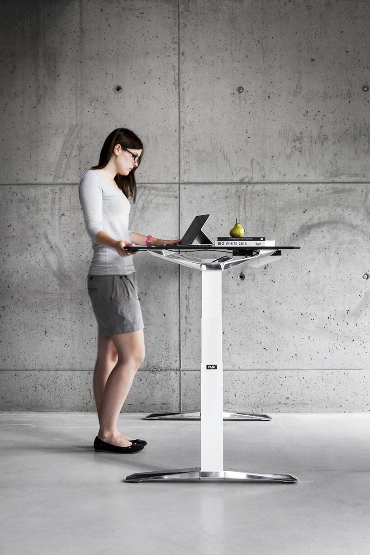 kobieta stojąca przy regulowanym biurku VANK_MOVE od VANK zregulacją wysokości na tle betonowej surowej ściany