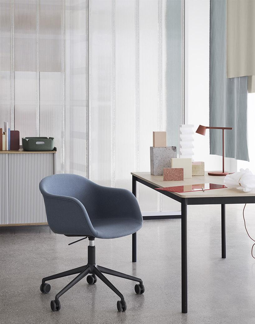 nowoczesny niebieski fotel Fiber od MUUTO na kółkach przy stoliku zjasnym blatem iczarnych nogach