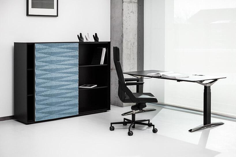 czarny elegancki Fotel VANK_FIL od VANK obok czarnej szafki zniebieskimi przesuwanymi drzwiczkamii czarnym elegancki biurku zregulacją wysokości
