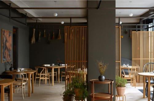 wnętrze restauracji w kolorze szarym z dodatkami jasnych drewnianych stolików