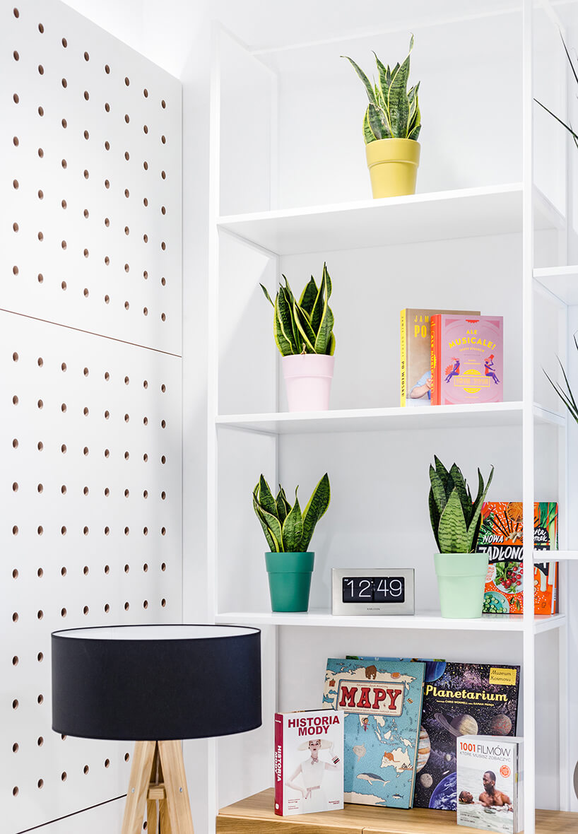 biała szafka zksiążkami ikwiatami na tle białej przestrzeni wpunkcie UPC