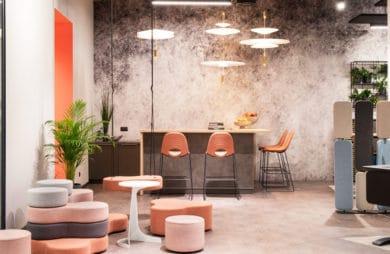 betonowa ściana przy stole i wysokich różowych krzesłach pod lampami okrągłymi