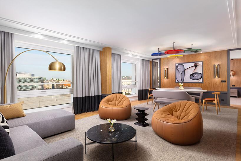 hotel Sofitel aranżacja apartamentu zdwoma pomarańczowymi siedziskami