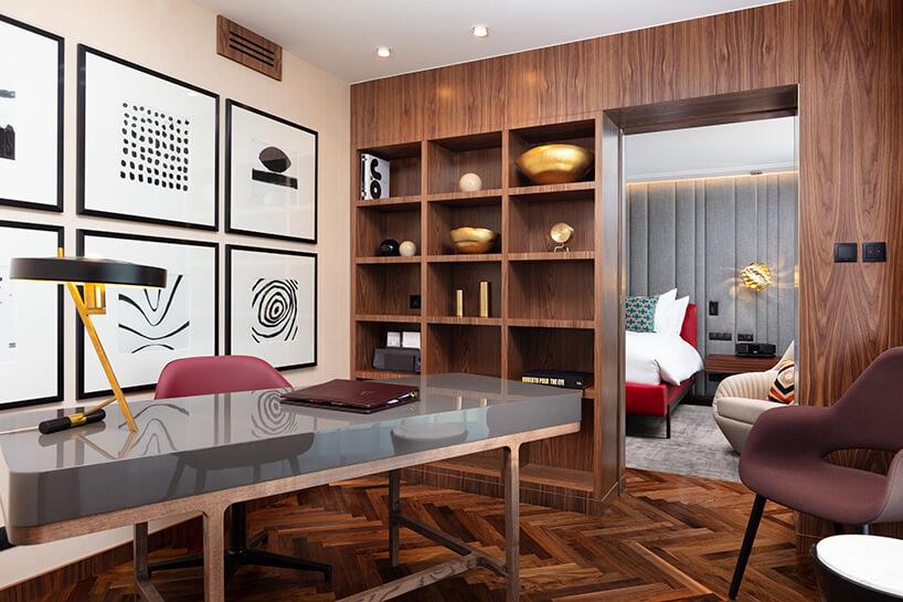 hotel Sofitel aranżacja apartamentu zszarym stołem idrewnianą zabudową