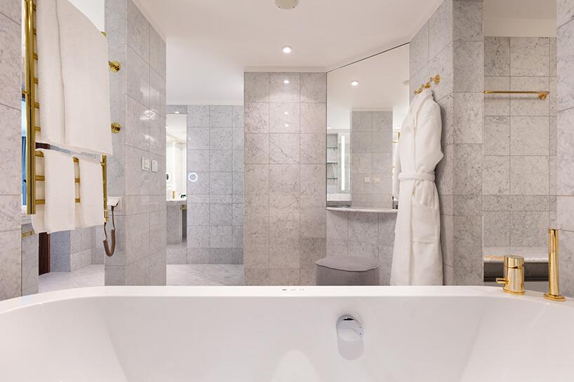 hotel Sofitel aranżacja apartamentu przestronnej łazienki wszarych kamiennych płytkach idodatkach wzłotym kolorze