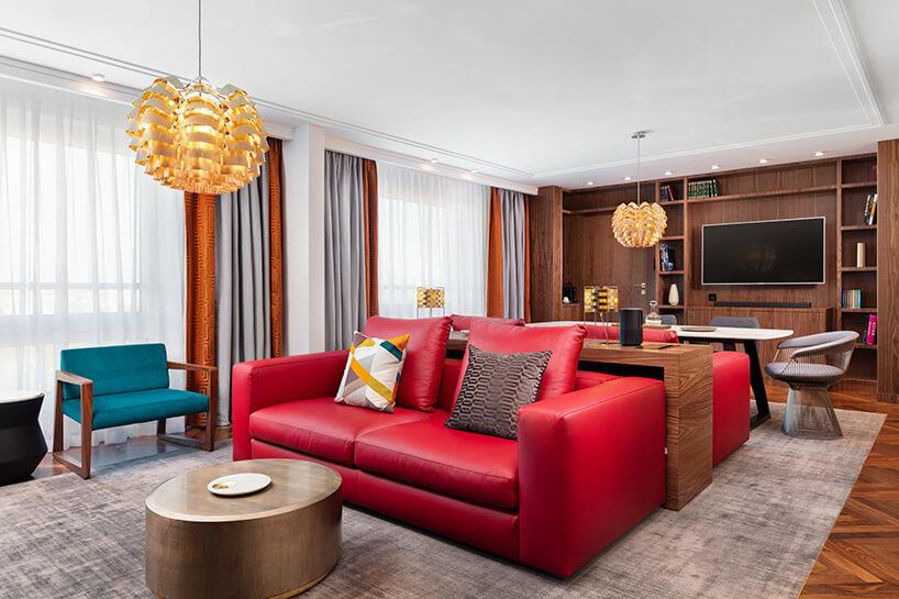 hotel Sofitel aranżacja apartamentu salonu zczerwoną sofą