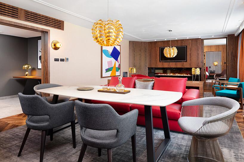 hotel Sofitel aranżacja apartamentu zwyjątkowym stołem zkamiennym blatem pod złotą lampą