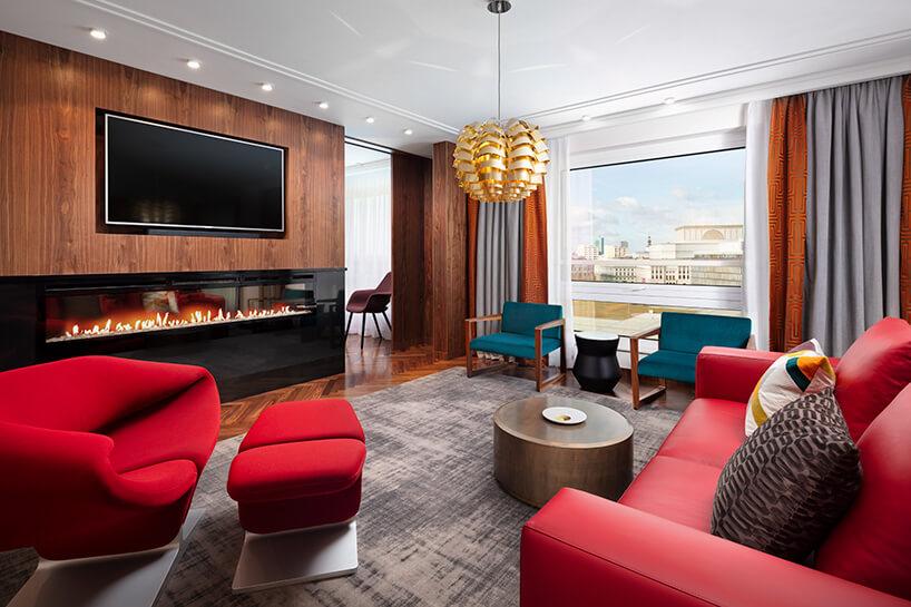 hotel Sofitel aranżacja apartamentu salonu zczerwoną sofą ifotelem