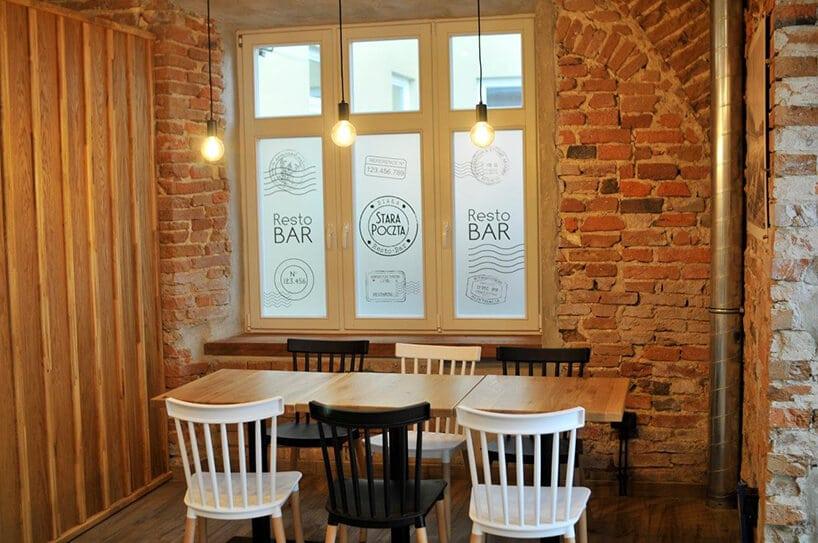 białe iczarne krzesła przy stole zdrewnianym blacie obok ściany zcegły