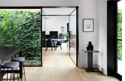 jasne wnętrze odrestaurowane ze szklaną ścianą z zielonym lasem w środku przy czarnym stole i krzesłach