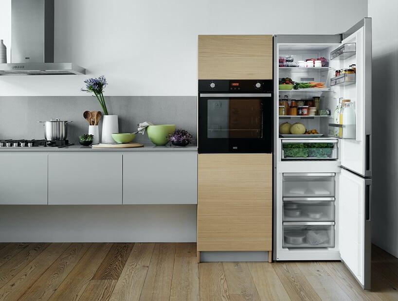 otwarte drzwi stalowej lodówki obok jasno drewnianego komina zciemnym piekarnikiem obok wiszących szafek kuchennych