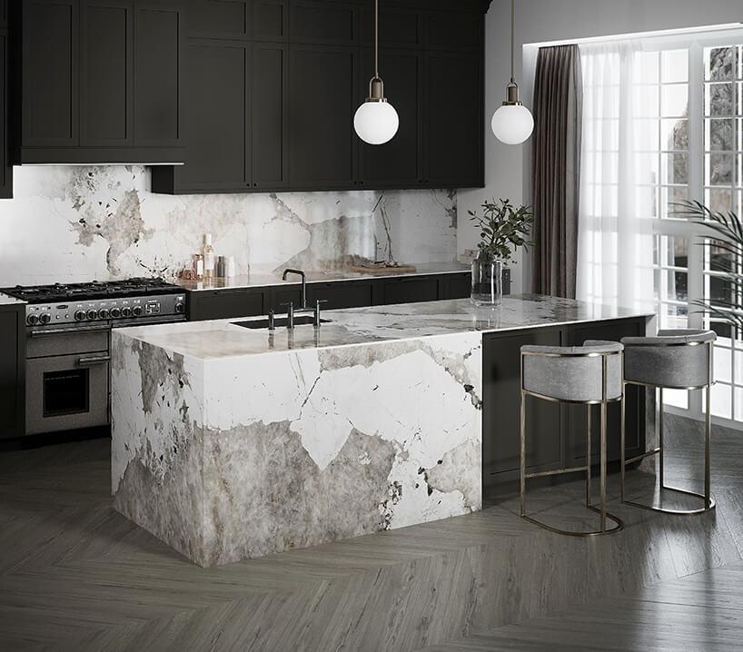 prostokątna wyspa kuchenna wykonana zbiałego marmuru oraz ciemna szarawa kuchnia zpłytkami zwzorem marmuru