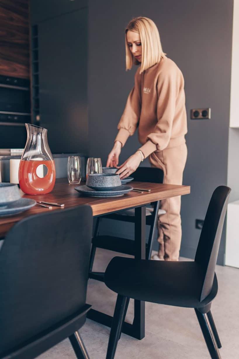 kobieta wbeżowym dresie przy stole zdrewniany blatem wszarej jadalni