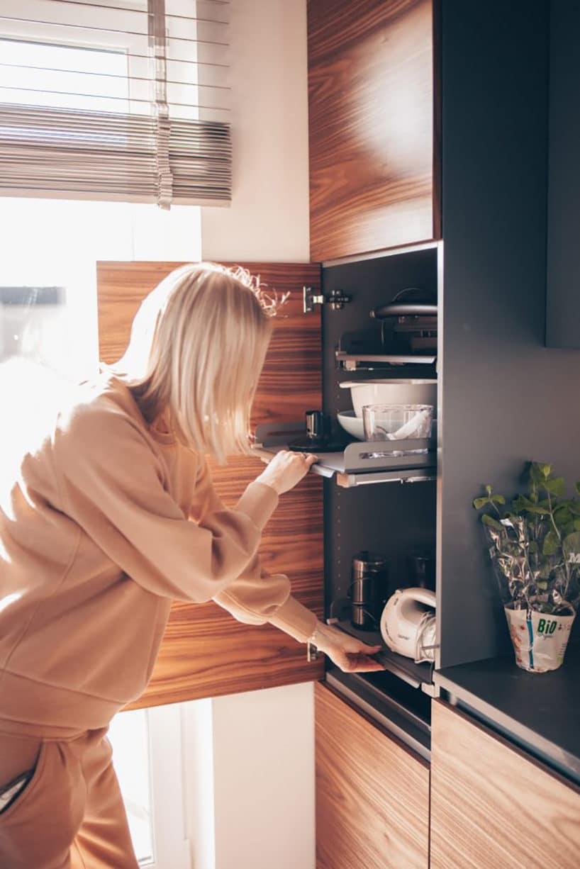 kobieta podczas wysuwania półek wszafce kuchennej zdrewnianym frontem
