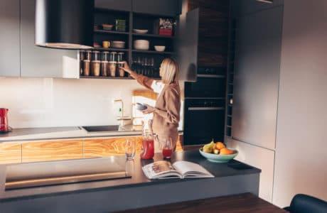 kobieta w nowoczesnej kuchni z szarymi frontami i ciemną wyspą