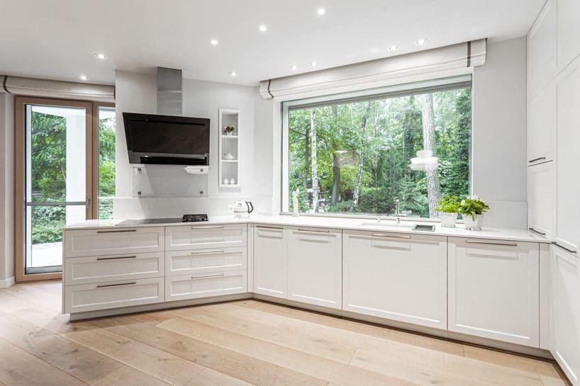 duża biała elegancka kuchnia S4 zkolekcji STYLE od ernestrust zzabudową pod ścianami zdużymi oknami