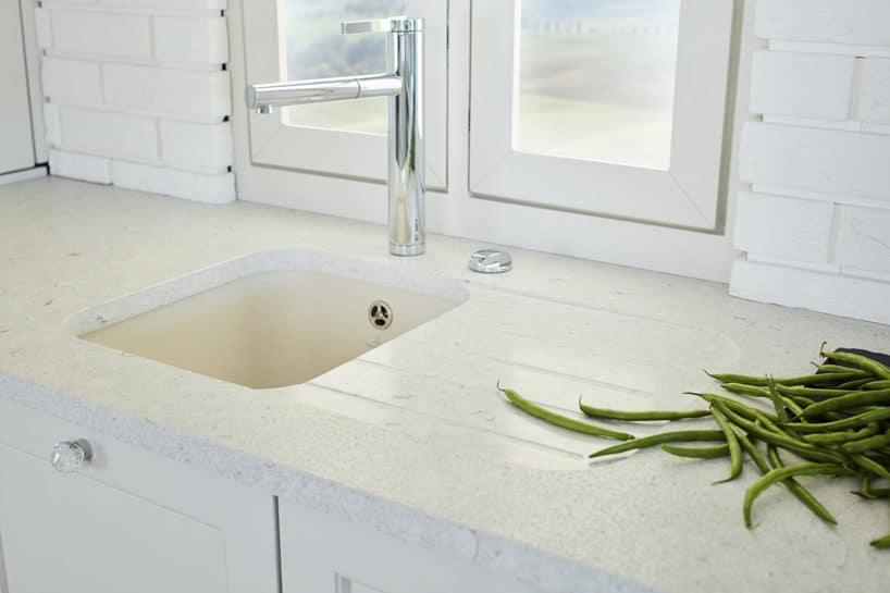 biała kuchnia S4 zkolekcji STYLE od ernestrust biały kamienny blat zbiałą zabudową zokrągłymi kryształowymi uchwytami