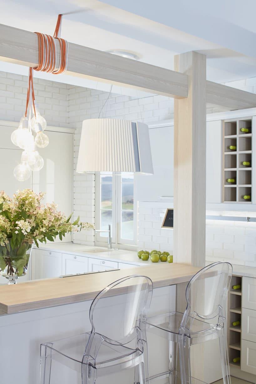 biała kuchnia S4 zkolekcji STYLE od ernestrust zmałą wyspą zdrewnianym blatem zdwoma plastikowymi przeźroczystymi krzesłami
