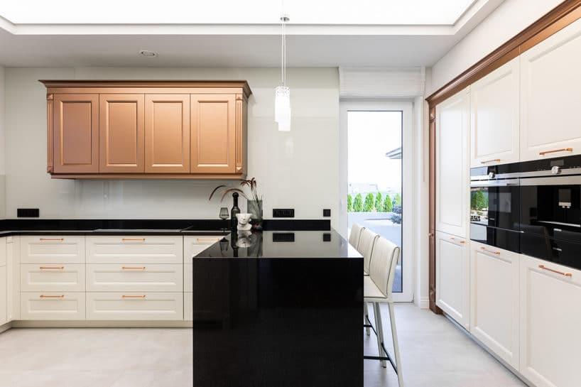 biała elegancka kuchnia od ernestrust zbiałą zabudową zczarnymi blatami idużą wyspą