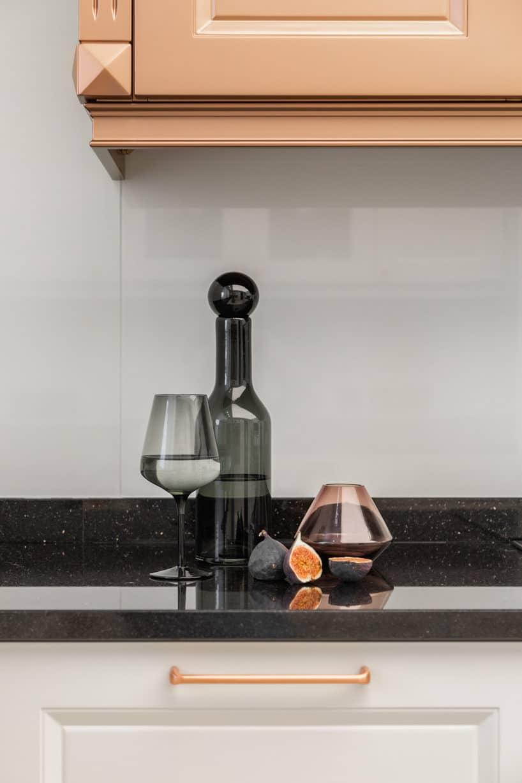 karafka zkieliszkiem zdymionego szkła na czarnym kamiennym blacie kuchennym
