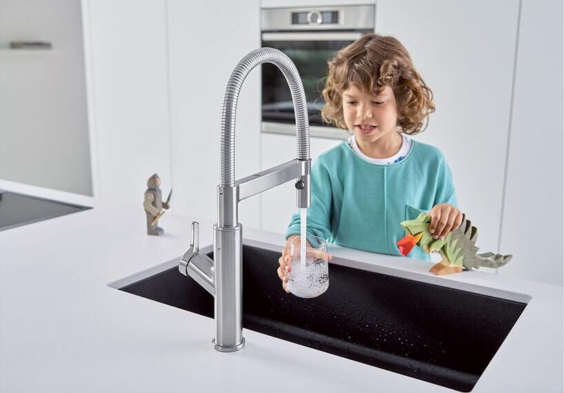 chłopiec nalewający wodę do szklanki zkranu wkuchni