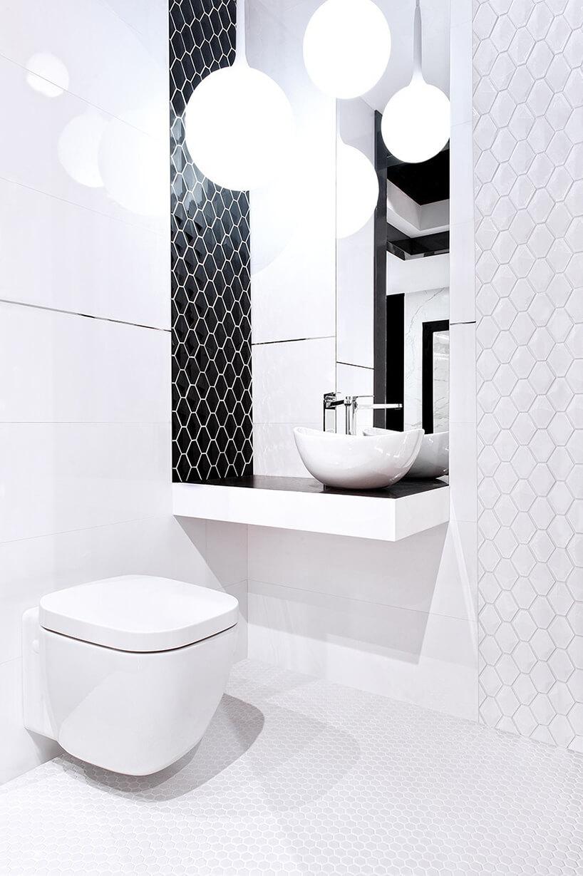 biała łazienka wsześciokątne płytki zjedną ścianą wczarne sześciokątne płytki