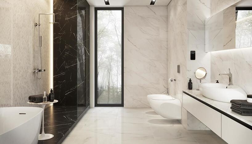biała łazienka wpłytkach zmotywem kamienia Carrara Pulpis od Opoczno zczarną kamienną częścią podłogi pod wanną inatryskiem