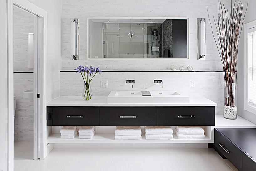 elegancka łazienka zdługim białym blatem zczarnymi szufladami pod dużym podłużnym lustrem na ścianie zbiałymi płytkami
