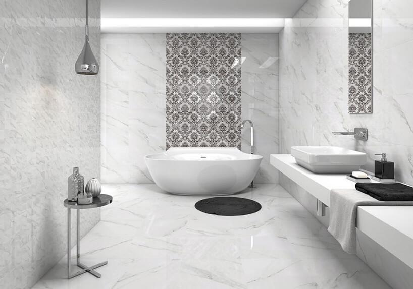 duża wanna wbiałej łazience zbiałym kamieniem na podłodze ina ścianach zciemnym motywem wycinanki za wanną