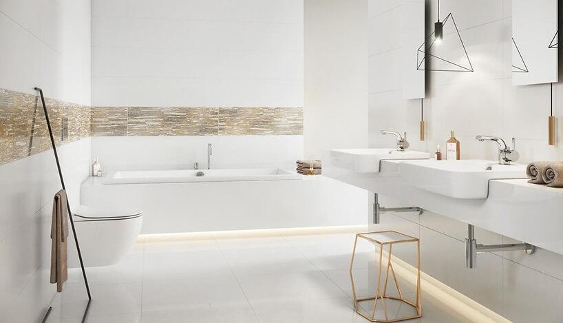 nowoczesna biała łazienka ze złotymi wykończeniami idużą zabudowaną wanną